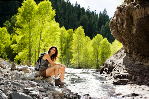 Woman sitting on rocks next to a river