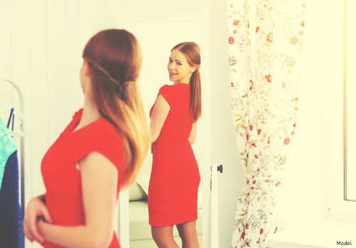 Woman in a red dress looking in the mirror