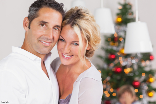Man and woman sitting next to a Christmas tree